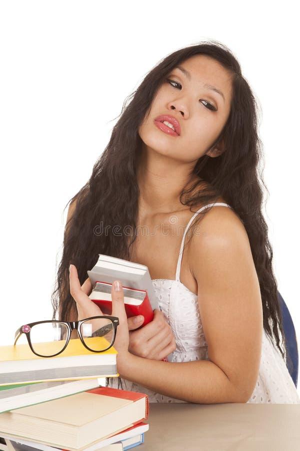 Os vidros asiáticos dos livros da mulher sentam-se fotos de stock