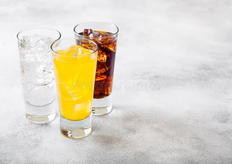Os vidros da soda bebem com cubos e bolhas de gelo no fundo de pedra da mesa de cozinha Cola e soda alaranjada da limonada imagens de stock royalty free