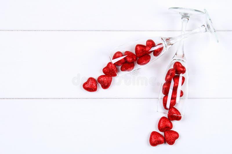 Os vidros de Champagne encheram-se com os corações cercados por rosas vermelhas em uma tabela de madeira branca Molde para o dia  fotografia de stock royalty free