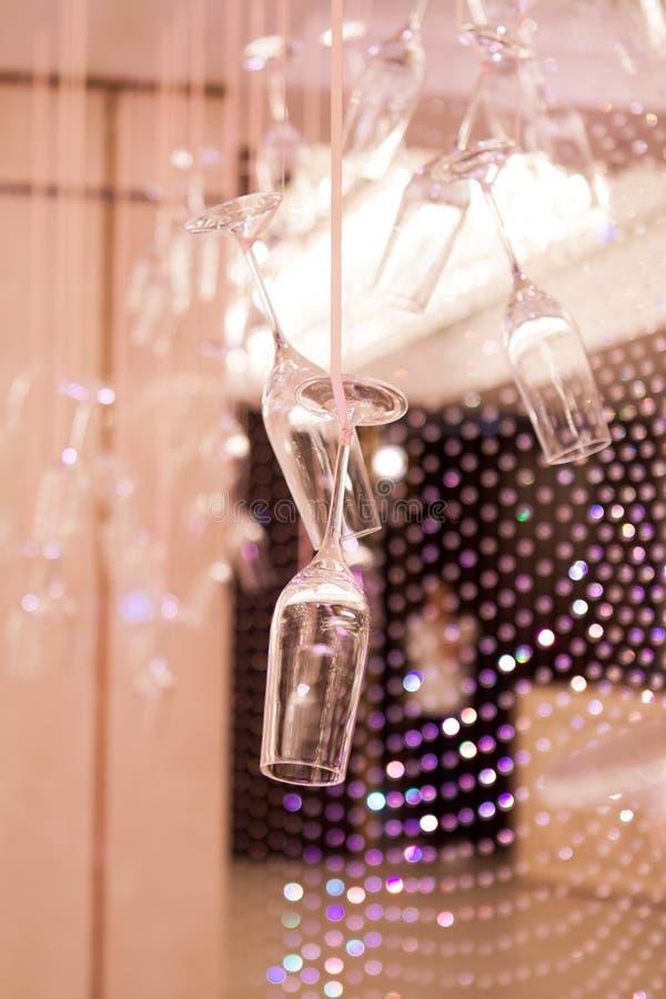 Os vidros de Champagne são pendurados para baixo em uma fita do cetim Ideias do casamento imagens de stock royalty free