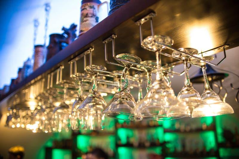 Os vidros de cocktail bonitos na barra penduram sobre a tabela nightclub As bebidas alcoólicas, muitos vidros de vinho têm formas foto de stock