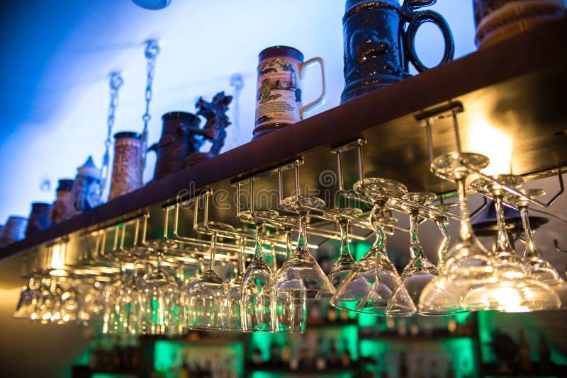Os vidros de cocktail bonitos na barra penduram sobre a tabela nightclub As bebidas alcoólicas, muitos vidros de vinho têm formas fotografia de stock