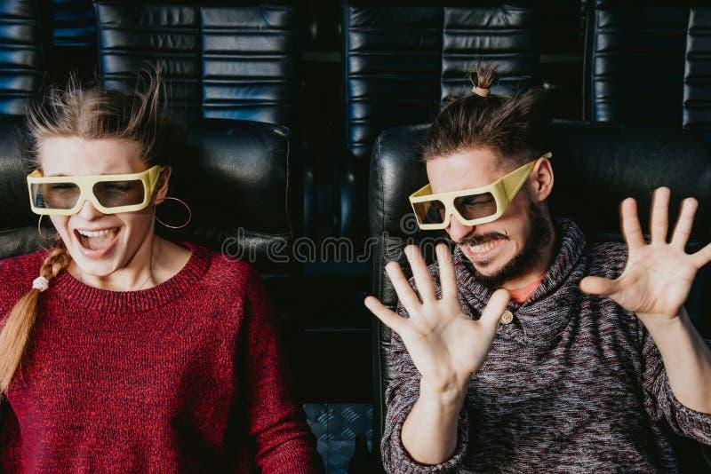 Os vidros do indivíduo e da menina 3d são preocupados muito ao olhar um filme imagem de stock royalty free
