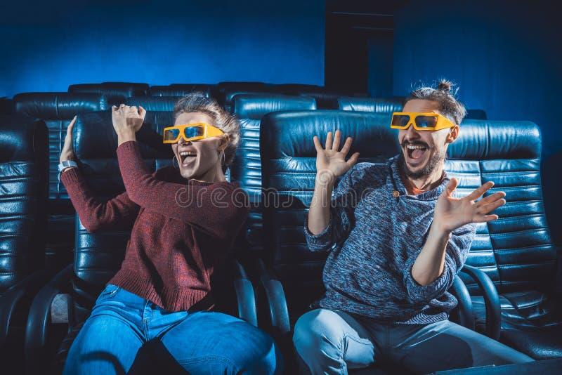 Os vidros do indivíduo e da menina 3d são preocupados muito ao olhar um filme imagens de stock