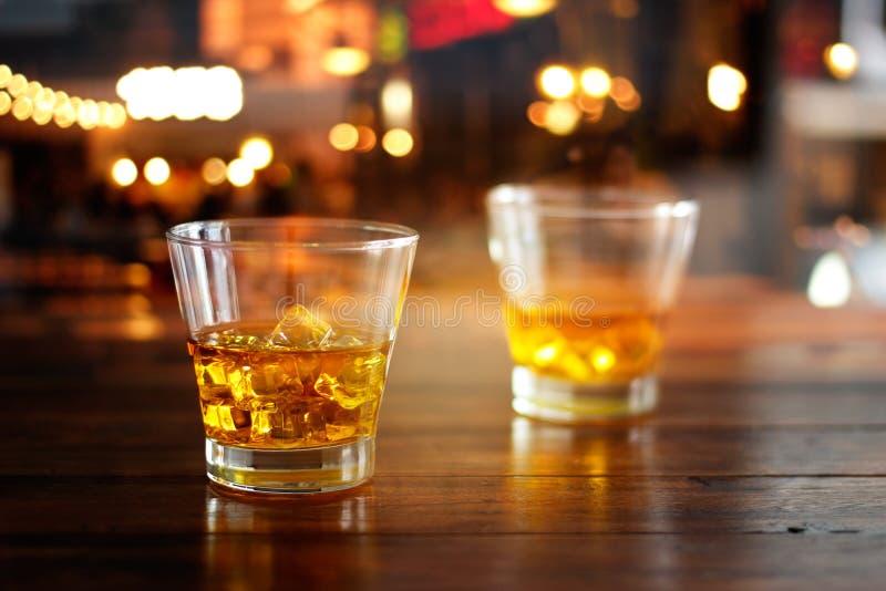 Os vidros do uísque bebem na tabela de madeira na noite colorida imagens de stock