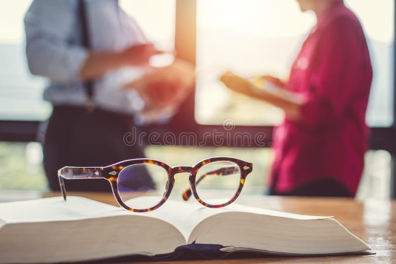 Os vidros do vintage, em livros empilham em público o livro da biblioteca, estudando o exame Livros do tutor com amigos imagens de stock royalty free