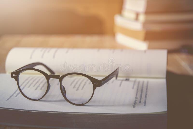 Os vidros do vintage, em livros empilham em p?blico o livro da biblioteca, estudando o exame fotos de stock