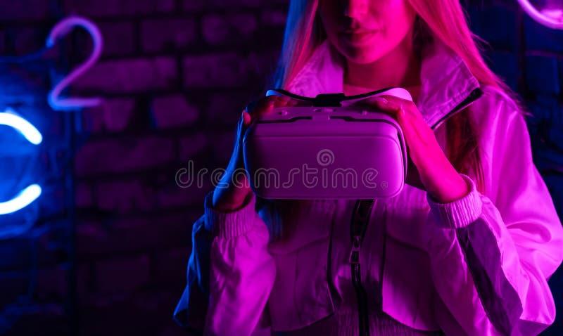 Os vidros do vr da posse do gamer da menina olham o vídeo 3d 360 na luz de néon roxa futurista fotos de stock royalty free