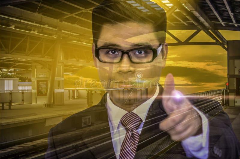Os vidros novos de Wear do homem de negócios esquadram, dedo que aponta para a frente no estação de caminhos-de-ferro do céu com  fotografia de stock royalty free