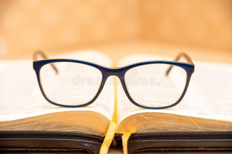 Os vidros para a mentira da vista na Bíblia, a Bíblia na tampa preta de couro com abas encontram-se na tabela fotografia de stock royalty free