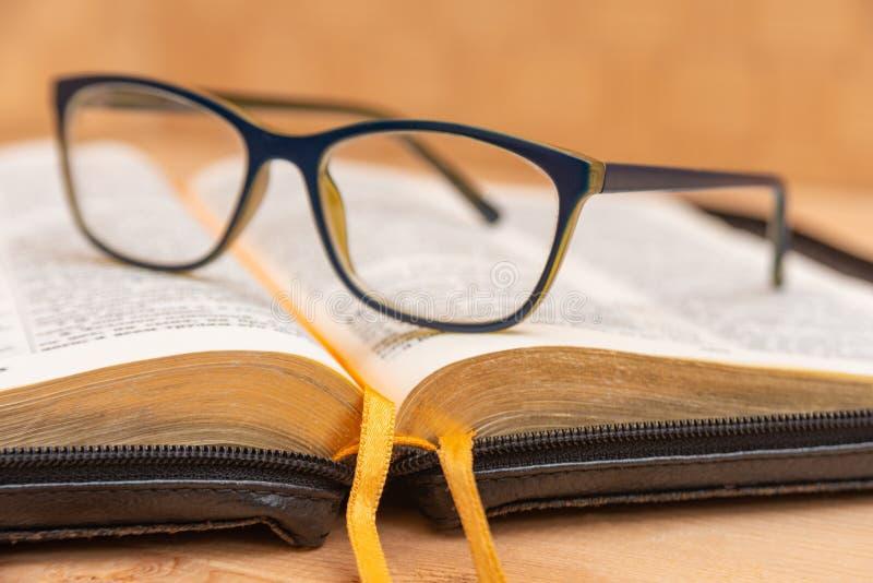 Os vidros para a mentira da vista na Bíblia, a Bíblia na tampa preta de couro com abas encontram-se na tabela foto de stock