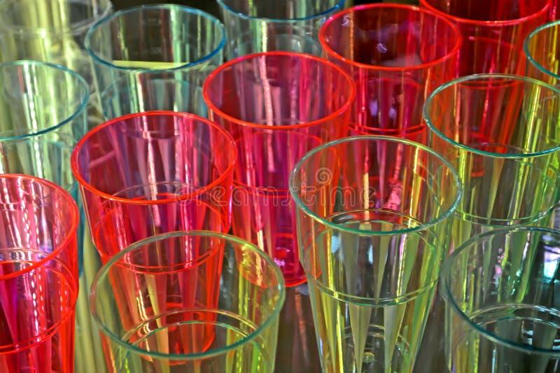 Os vidros plásticos do arco-íris embalam o close up, diversidade colorida da fabricação, imagens de stock