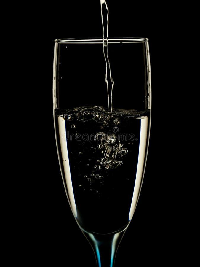 Os vidros são derramados com agua potável imagens de stock