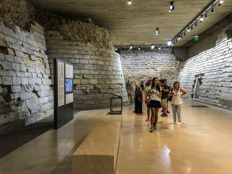 Os visitantes estudam uma parcela do Louvre medieval como preservado no museu moderno, Paris, França foto de stock royalty free