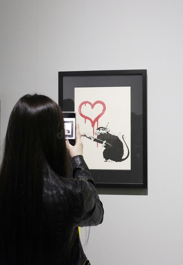 Os visitantes tomam fotos em uma exposi??o desautorizada de Banksy fotografia de stock royalty free
