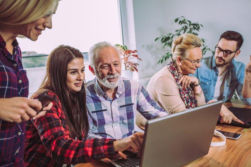Os voluntários ajudam povos superiores no computador imagem de stock royalty free