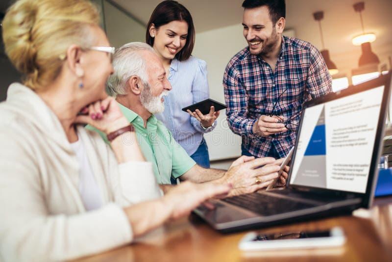 Os voluntários ajudam povos superiores no computador Jovens que dão a introdução superior dos povos ao Internet foto de stock royalty free