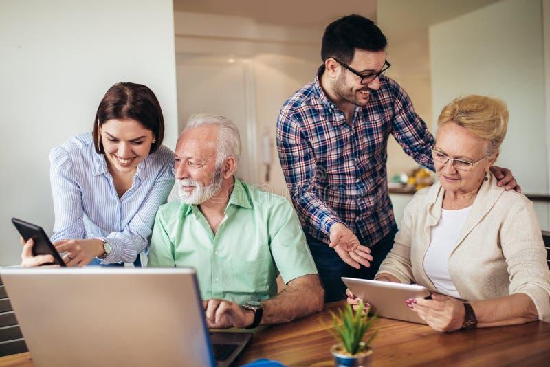 Os voluntários ajudam povos superiores no computador Jovens que dão a introdução superior dos povos ao Internet imagem de stock royalty free