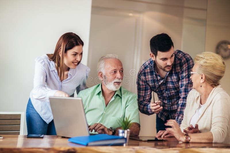 Os voluntários ajudam povos superiores no computador Jovens que dão a introdução superior dos povos ao Internet fotografia de stock royalty free