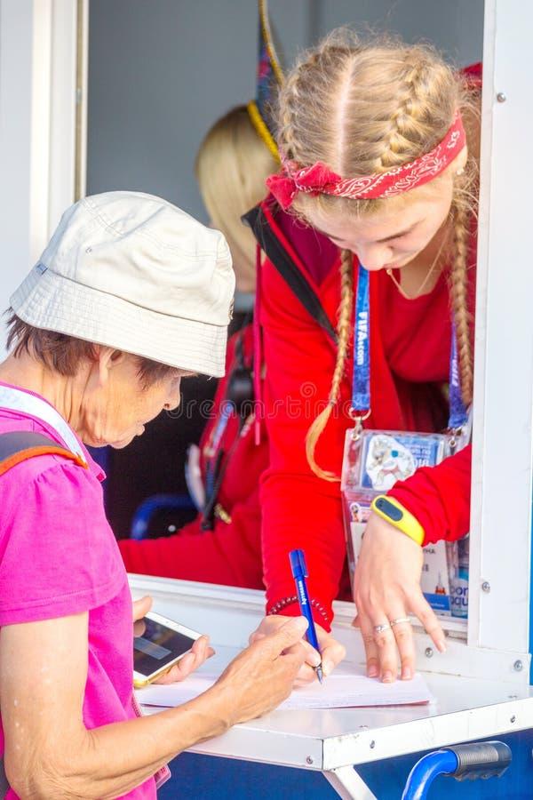 os voluntários bonitos das meninas ajudam um fan de futebol velho no campeonato do mundo imagem de stock