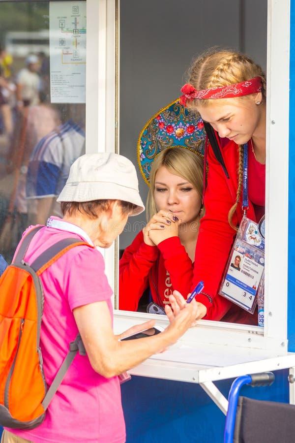 os voluntários bonitos das meninas ajudam um fan de futebol velho no campeonato do mundo fotos de stock