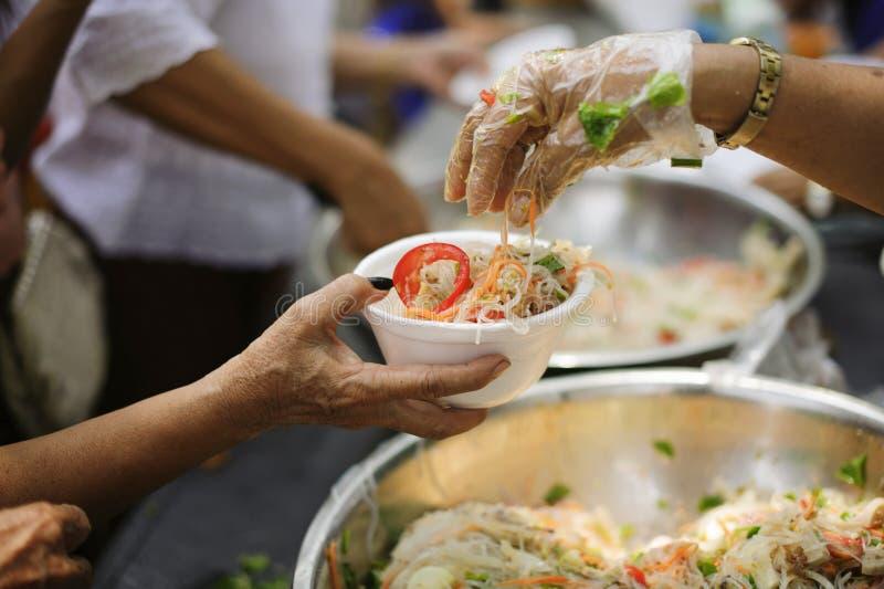 Os voluntários dão o alimento aos pobres: doar o alimento está ajudando amigos humanos na sociedade: Povos de ajuda com fome com  fotografia de stock