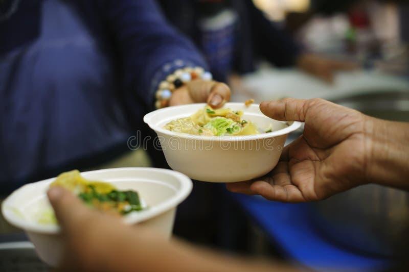 Os voluntários dão o alimento aos pobres: doar o alimento está ajudando amigos humanos na sociedade: Povos de ajuda com fome com  fotos de stock