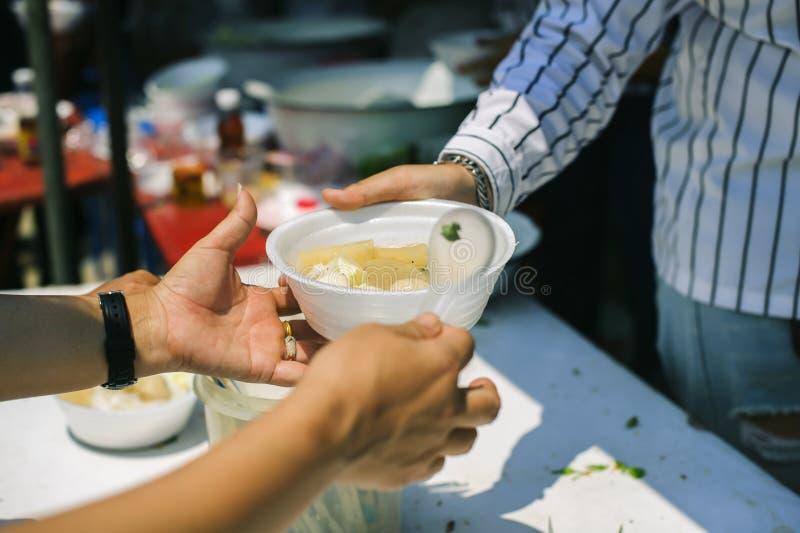 Os voluntários dão o alimento aos pobres: doar o alimento está ajudando amigos humanos na sociedade: Povos de ajuda com fome com  imagens de stock