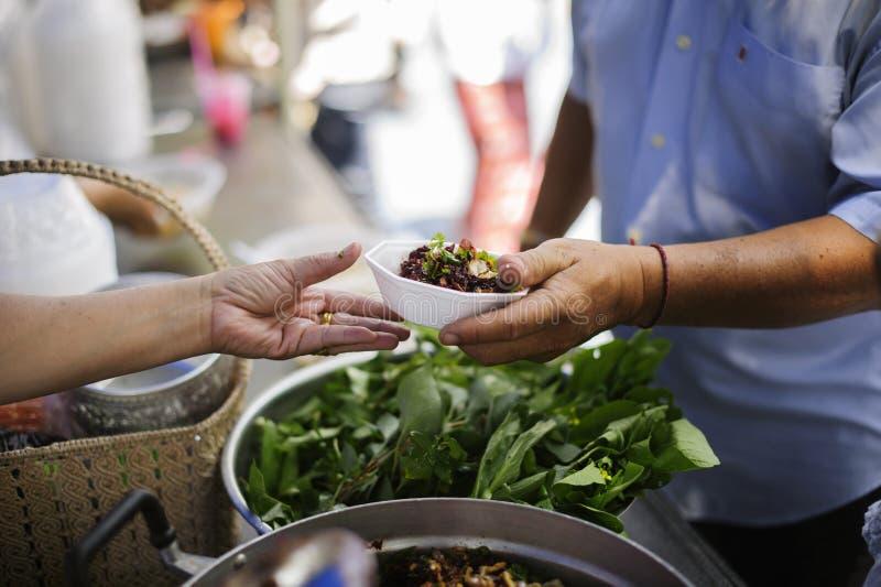 Os voluntários dão o alimento aos pobres: doar o alimento está ajudando amigos humanos na sociedade: Povos de ajuda com fome com  imagens de stock royalty free