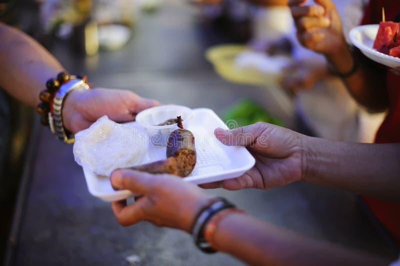 Os voluntários dão o alimento aos pobres: doar o alimento está ajudando amigos humanos na sociedade: Povos de ajuda com fome com  foto de stock royalty free