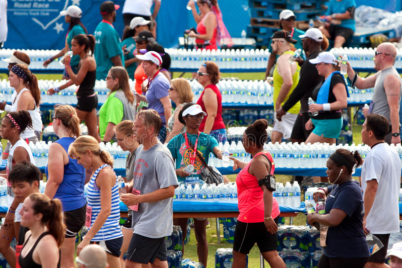 Os voluntários distribuem garrafas de água aos corredores esgotados após a raça imagens de stock royalty free