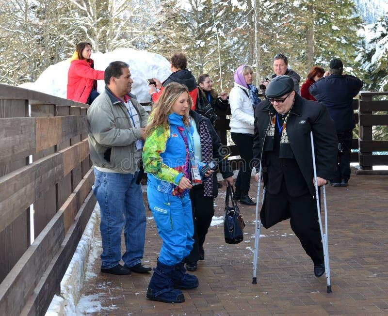 Os voluntários do transporte ajudam fãs com inabilidades no conjunto da montanha imagens de stock