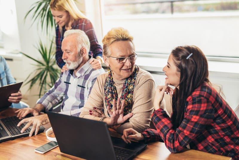 Os voluntários novos ajudam povos superiores no computador fotos de stock royalty free