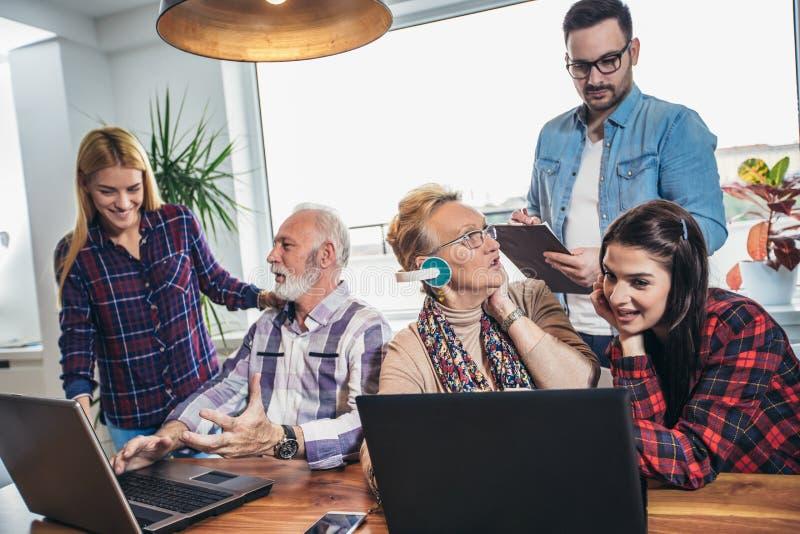 Os voluntários novos ajudam povos superiores no computador imagens de stock royalty free