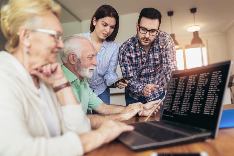 Os voluntários novos ajudam povos superiores no computador imagens de stock