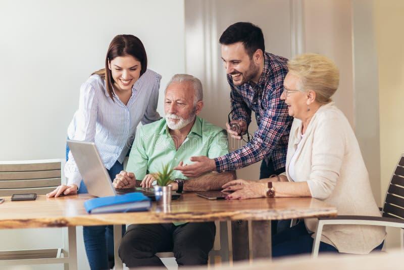 Os voluntários novos ajudam povos superiores no computador imagem de stock