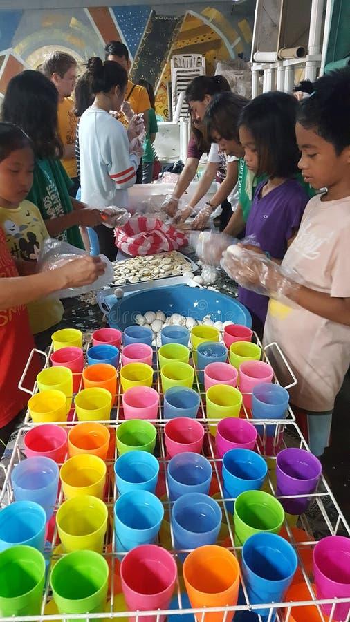 Os voluntários preparam o alimento para o programa de alimentação em uma comunidade do precário imagens de stock