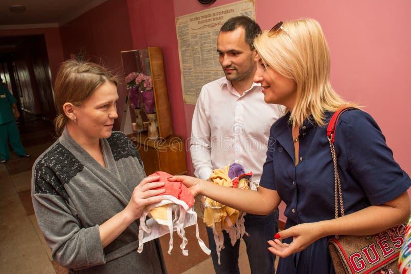 Os voluntários team doando a roupa para bebês à mãe nova na casa de maternidade durante o dia da proteção das crianças fotografia de stock royalty free