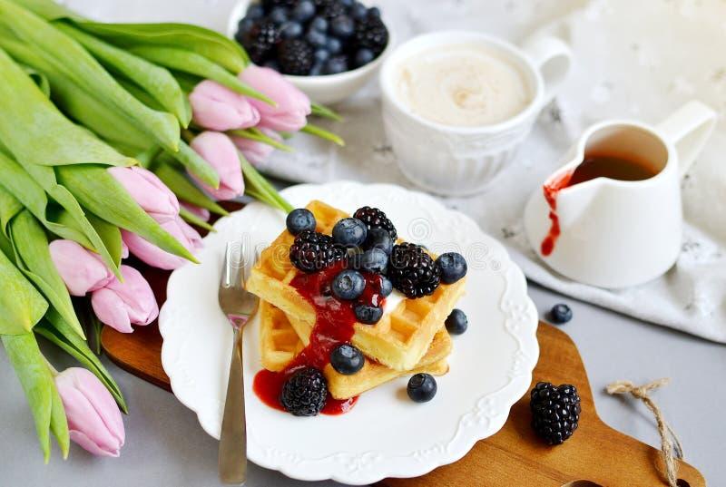 Os waffles belgas caseiros com as bagas do molho de creme, copo com bebida do cappuccino florescem tulipas cor-de-rosa, Gray Back fotografia de stock