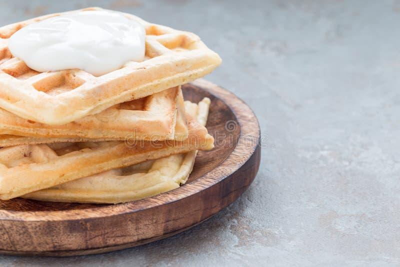 Os waffles belgas saborosos caseiros com o bacon e o queijo shredded, servidos com o iogurte liso na placa de madeira, horizontal foto de stock royalty free