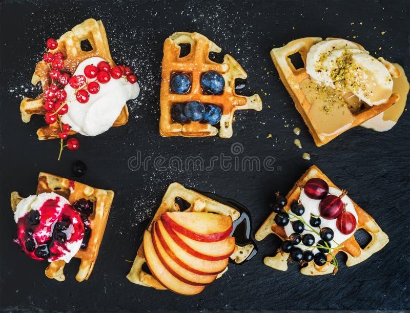 Os waffles caseiros belgas mornos com as bagas do jardim, fruto e gelado frescos na ardósia escura apedrejam o fundo imagem de stock