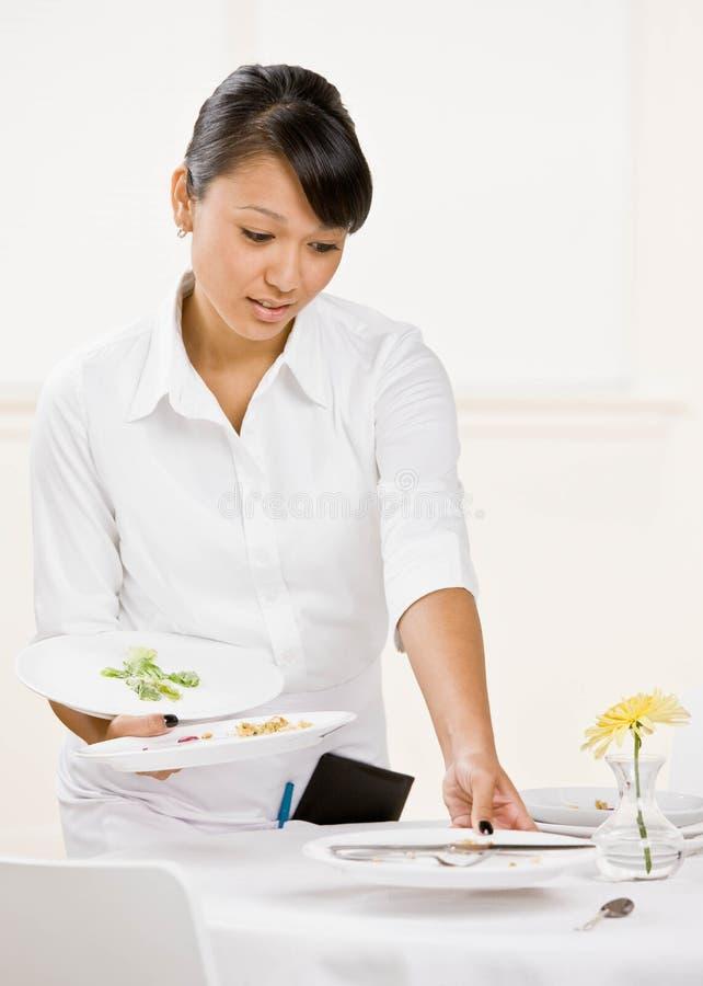 Os waiterss fêmeas limpam placas sujas fotos de stock