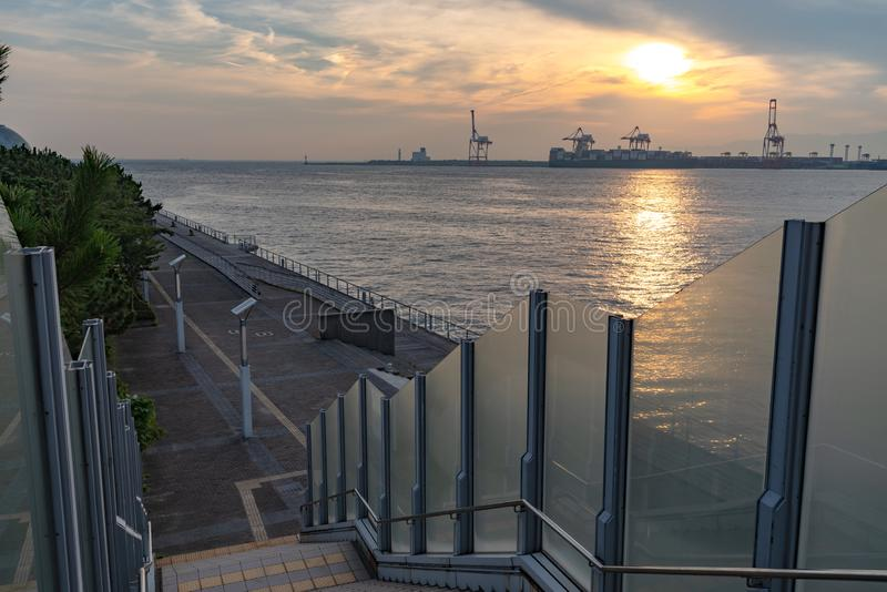 Osaka bay with Yumeshima island on background in summer sun set time. View from Osaka metro Cosmosquare train station park promenade royalty free stock photography