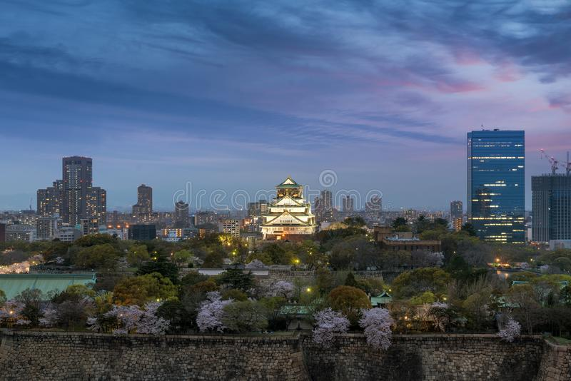 Osaka castle with cherry blossom and center business district in. Background at Osaka, Japan. Japan spring beautiful scene stock photography