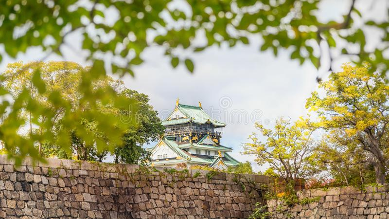Osaka Castle top roof seen in the distance above the stone wall fortification in Japan. stock images