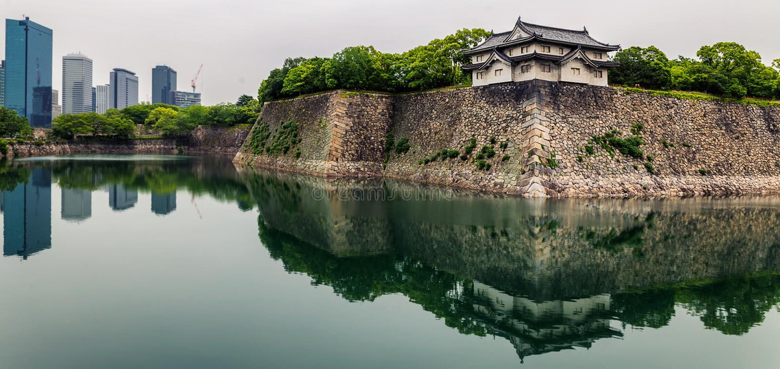 Osaka castle walls and modern office buildings with reflections in moat. Japan stock photo
