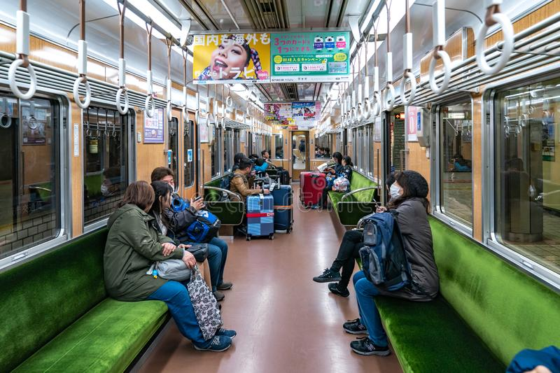 Osaka, Giappone - 3 marzo 2018: I passeggeri non camminano e si siedono nel treno sotterraneo locale del Giappone non 8984 ed and fotografie stock libere da diritti