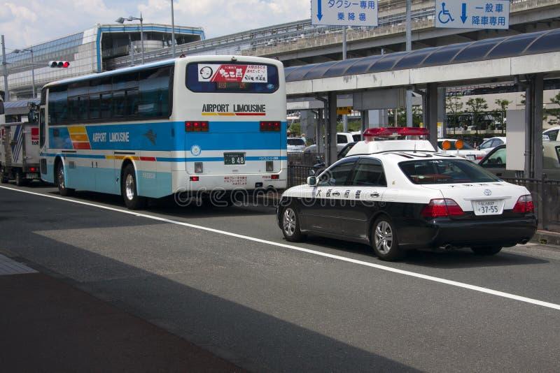 OSAKA, JAPÃO - 10 DE AGOSTO: Ônibus de limusina do aeroporto e carro de polícia em O fotografia de stock