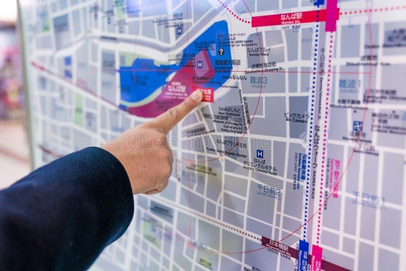 Osaka, Japão - 3 de março de 2018: O viajante lê e para apontar ao mapa do trem do metro do metro do Japão na placa , na área de  foto de stock royalty free