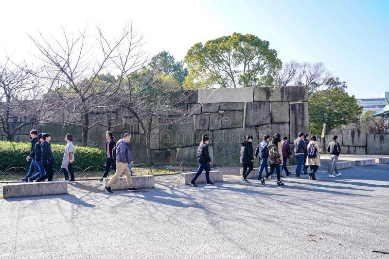 Osaka, Japón - 4 de marzo de 2018: El japonés, turistas, viajeros caminó alrededor del parque de Osaka Castle en marzo de 2018 co imagenes de archivo